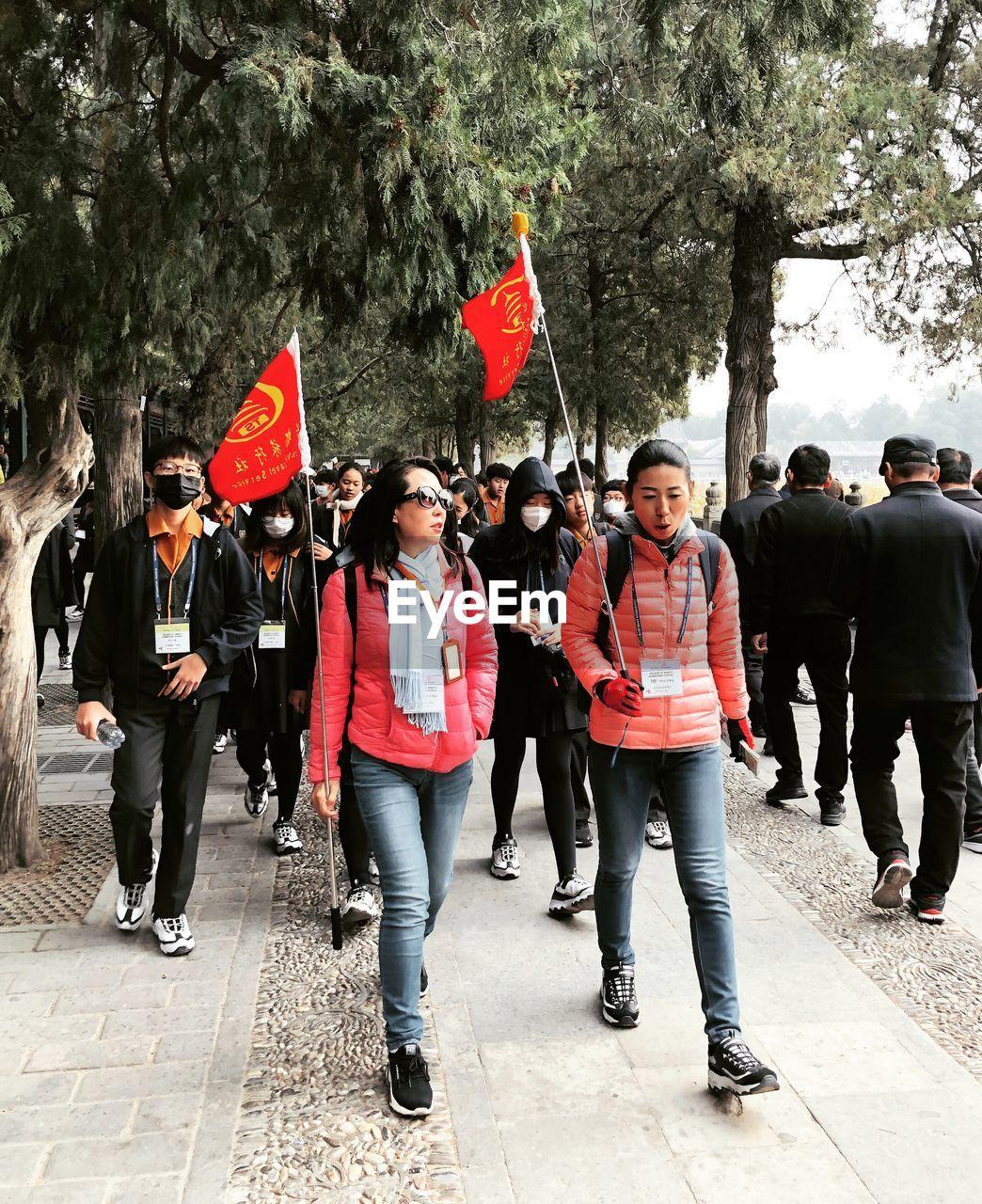 GROUP OF PEOPLE WALKING ON LEAVES