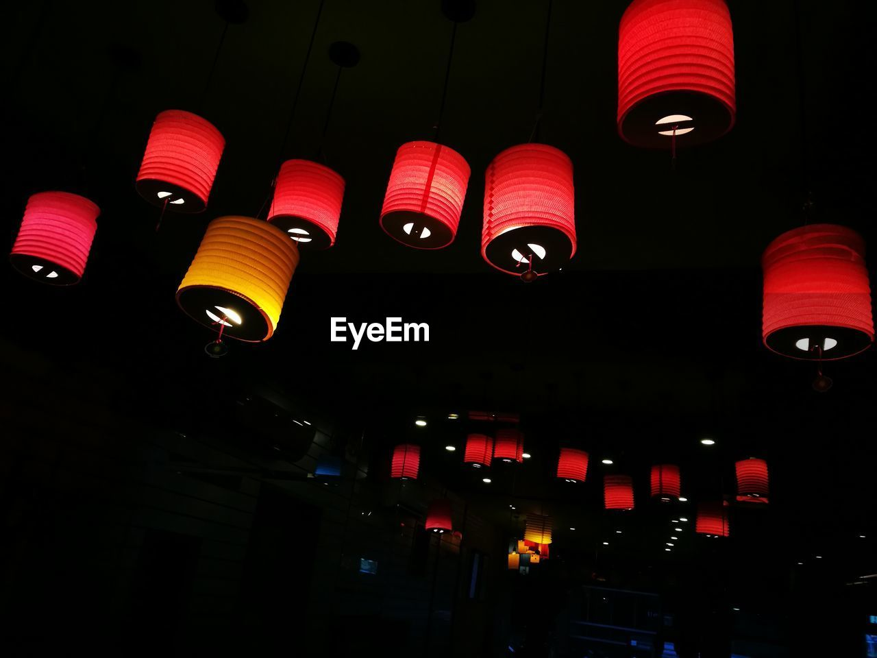 LOW ANGLE VIEW OF ILLUMINATED LANTERNS HANGING ON THE WALL