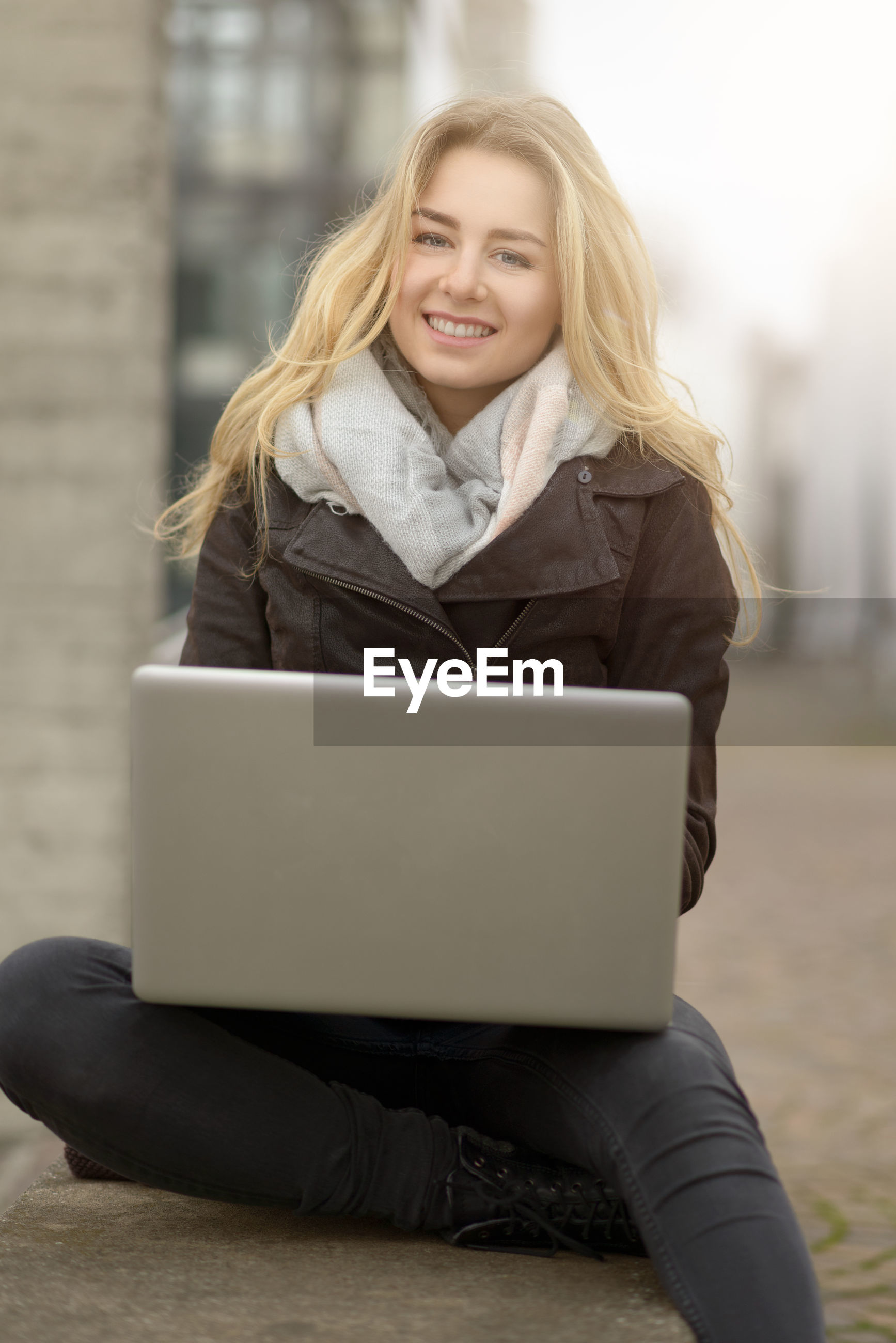 Portrait of smiling young woman with blond hair using laptop outdoors