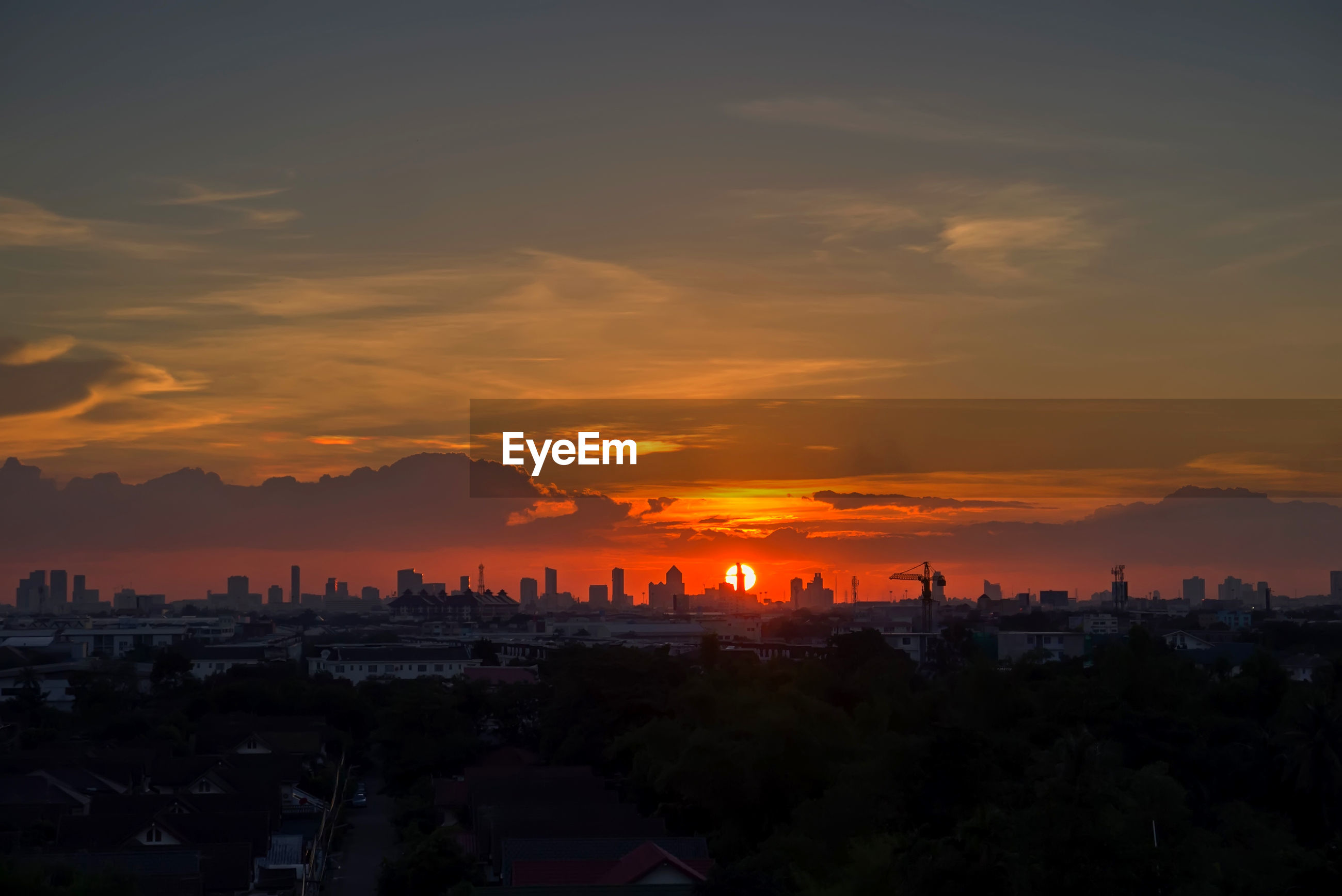HIGH ANGLE VIEW OF SILHOUETTE BUILDINGS AGAINST ORANGE SKY