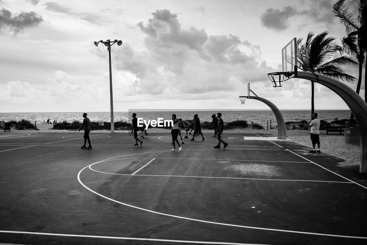sky, sport, group of people, nature, cloud - sky, men, basketball - sport, real people, people, court, leisure activity, playing, street light, day, outdoors, water, crowd, lifestyles, competition