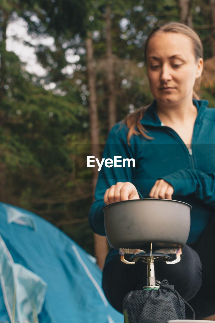 Woman Preparing Food At Camping Site