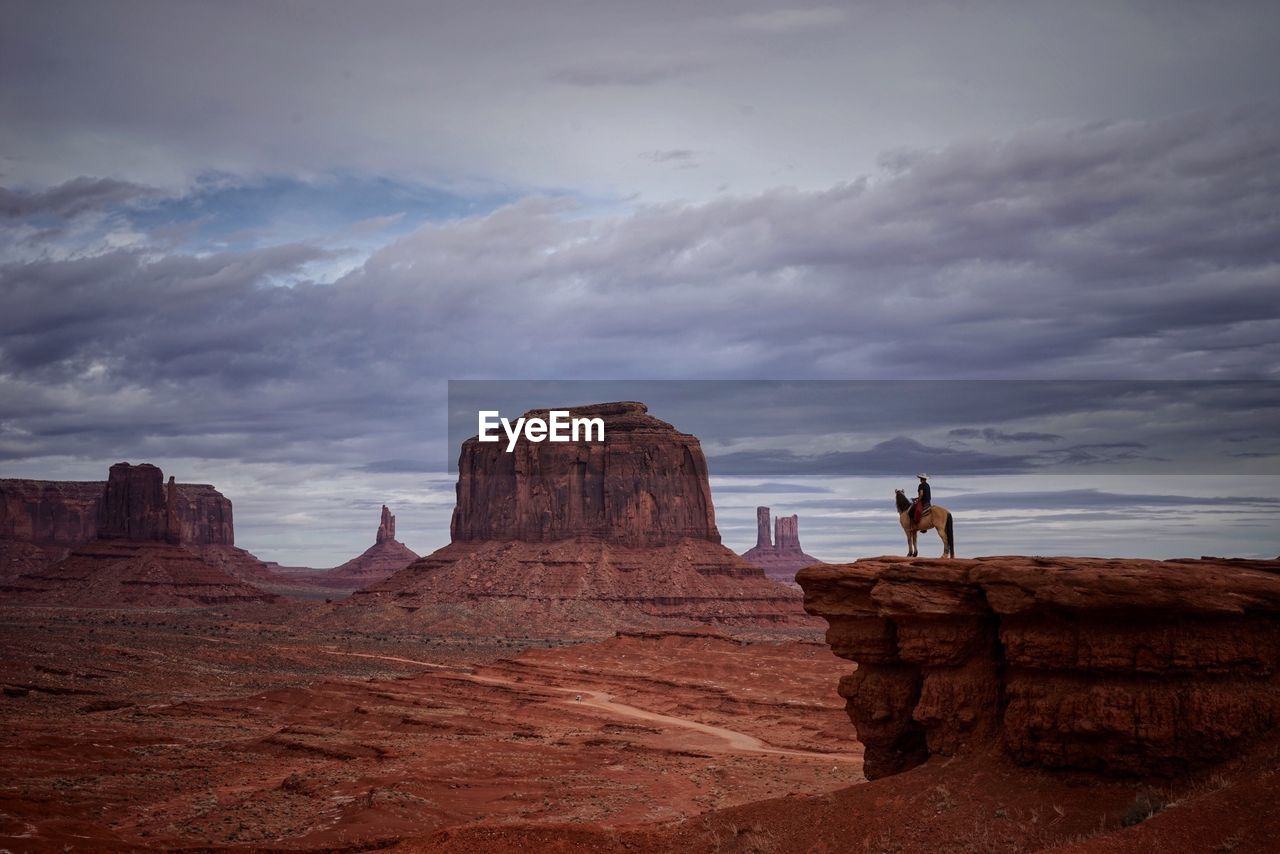Man With Horse On Cliff By Rock Formations Against Cloudy Sky At Monument Valley