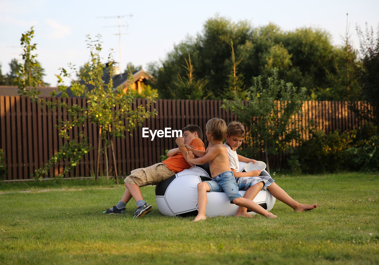 Boys Playing On Bean Bag In Yard