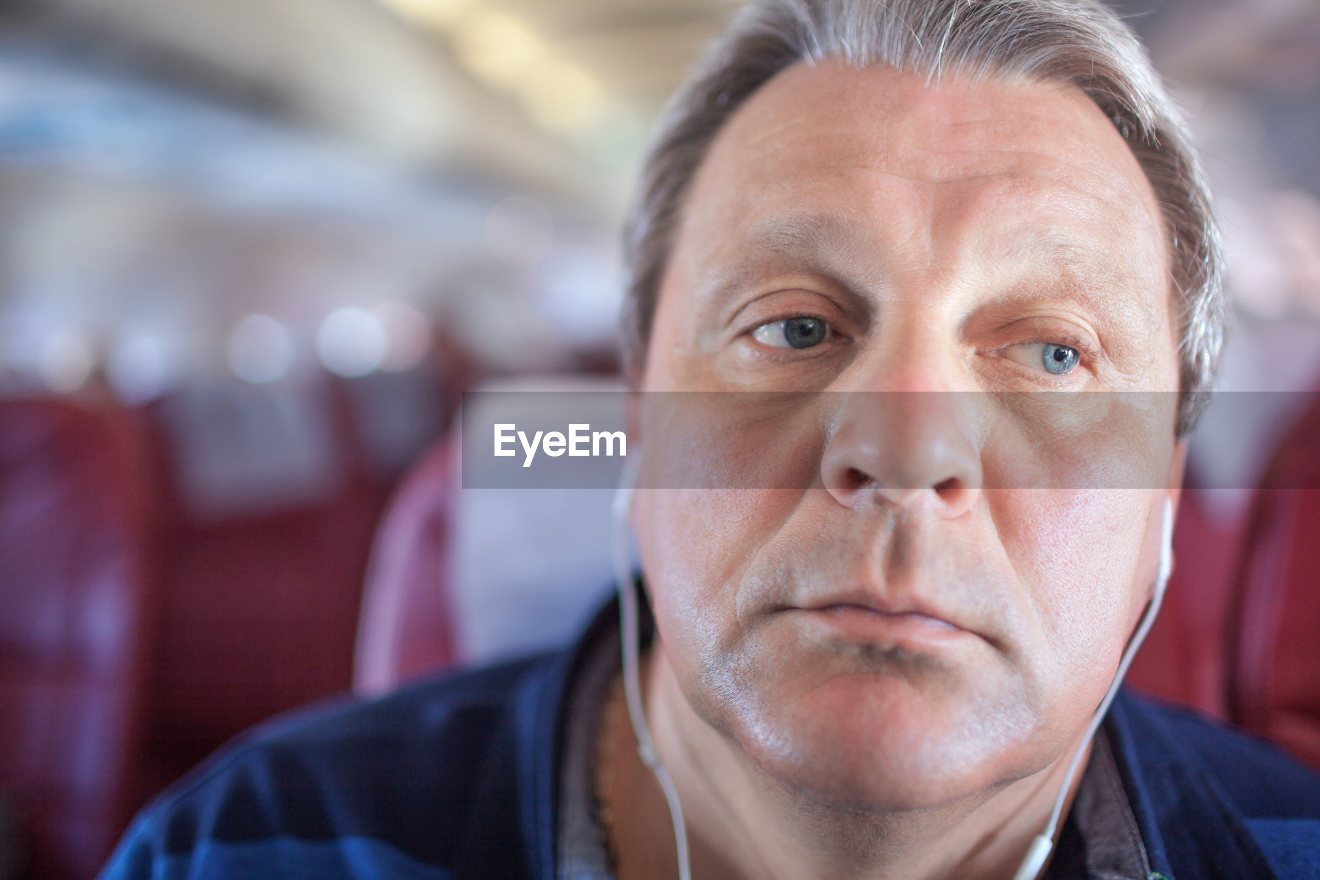 Close-up of mature man listening music while sitting in airplane
