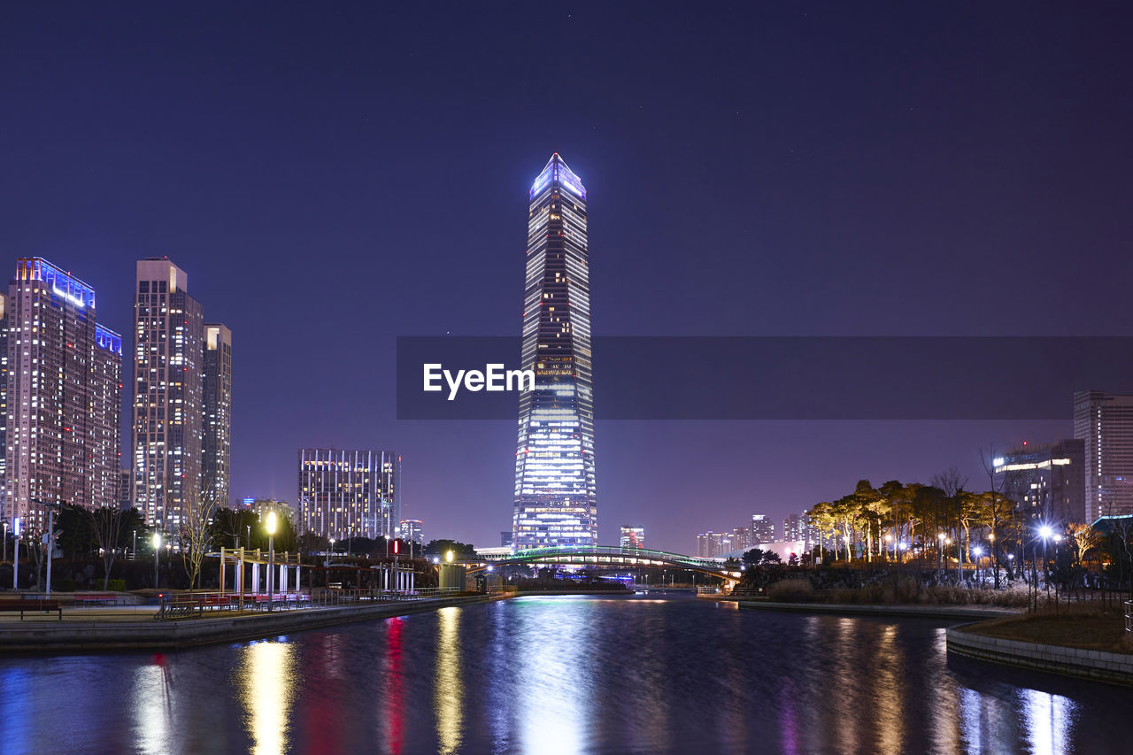architecture, building exterior, night, built structure, illuminated, city, office building exterior, sky, tall - high, water, skyscraper, building, waterfront, travel destinations, tower, landscape, river, nature, office, modern, no people, cityscape, outdoors, financial district, nightlife