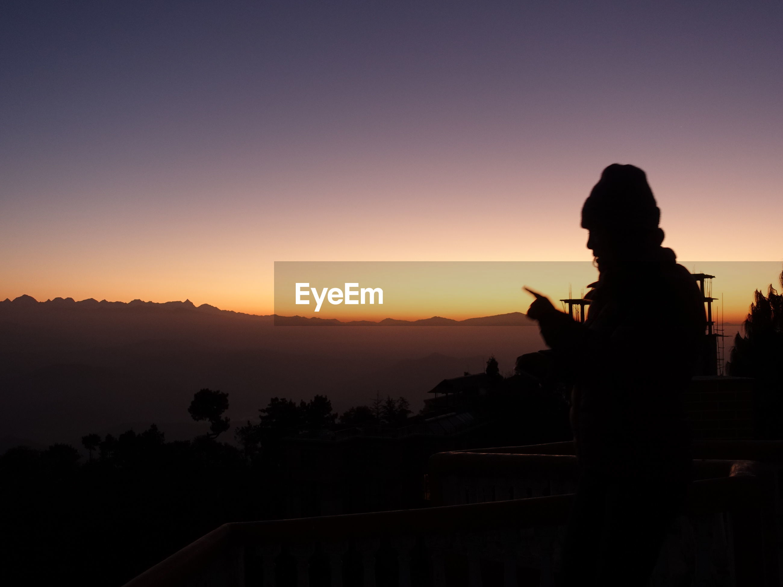 SILHOUETTE MAN STANDING BY MOUNTAINS AGAINST ORANGE SKY