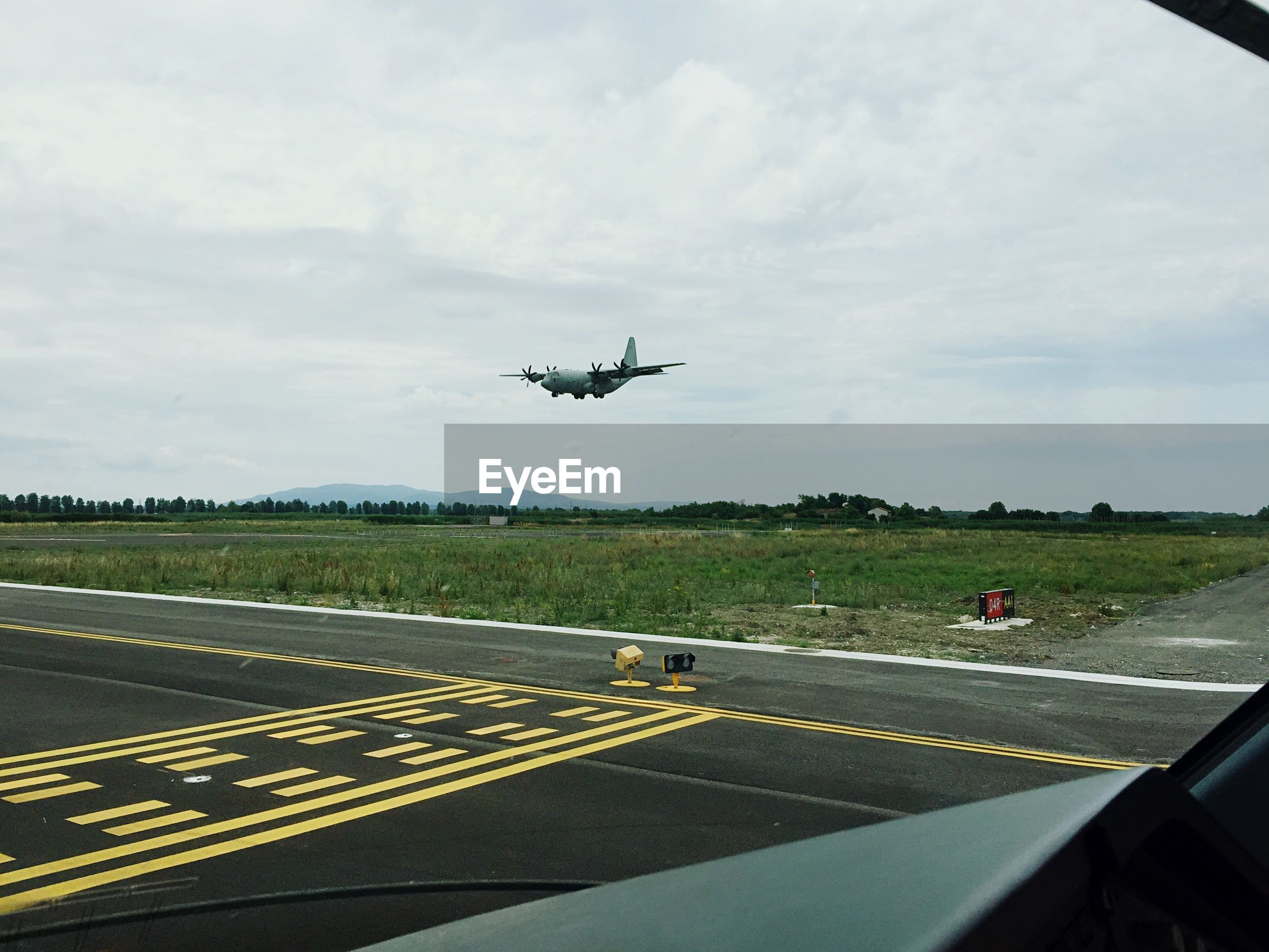 Airplane over runway seen from windshield against sky