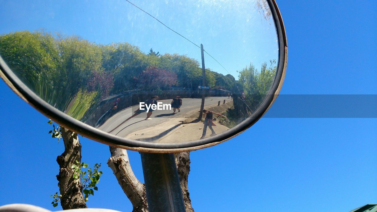 Reflection of people in mirror against clear blue sky