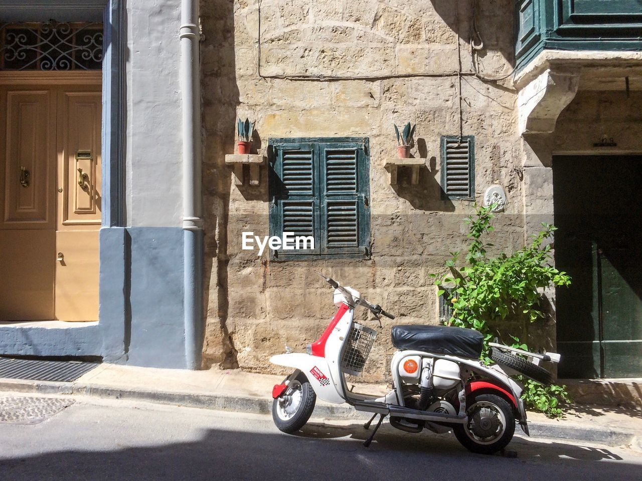 building exterior, architecture, built structure, transportation, mode of transportation, land vehicle, day, building, scooter, sunlight, city, window, street, outdoors, residential district, motor scooter, shadow, stationary, motor vehicle, car