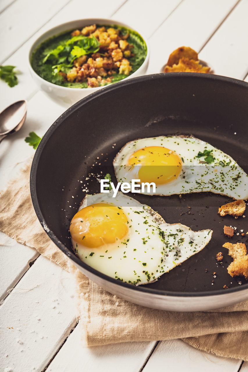 egg, food, food and drink, ready-to-eat, healthy eating, freshness, kitchen utensil, indoors, fried egg, wellbeing, table, fried, meal, breakfast, no people, still life, household equipment, egg yolk, high angle view, vegetable, frying pan, sunny side up, vegetarian food
