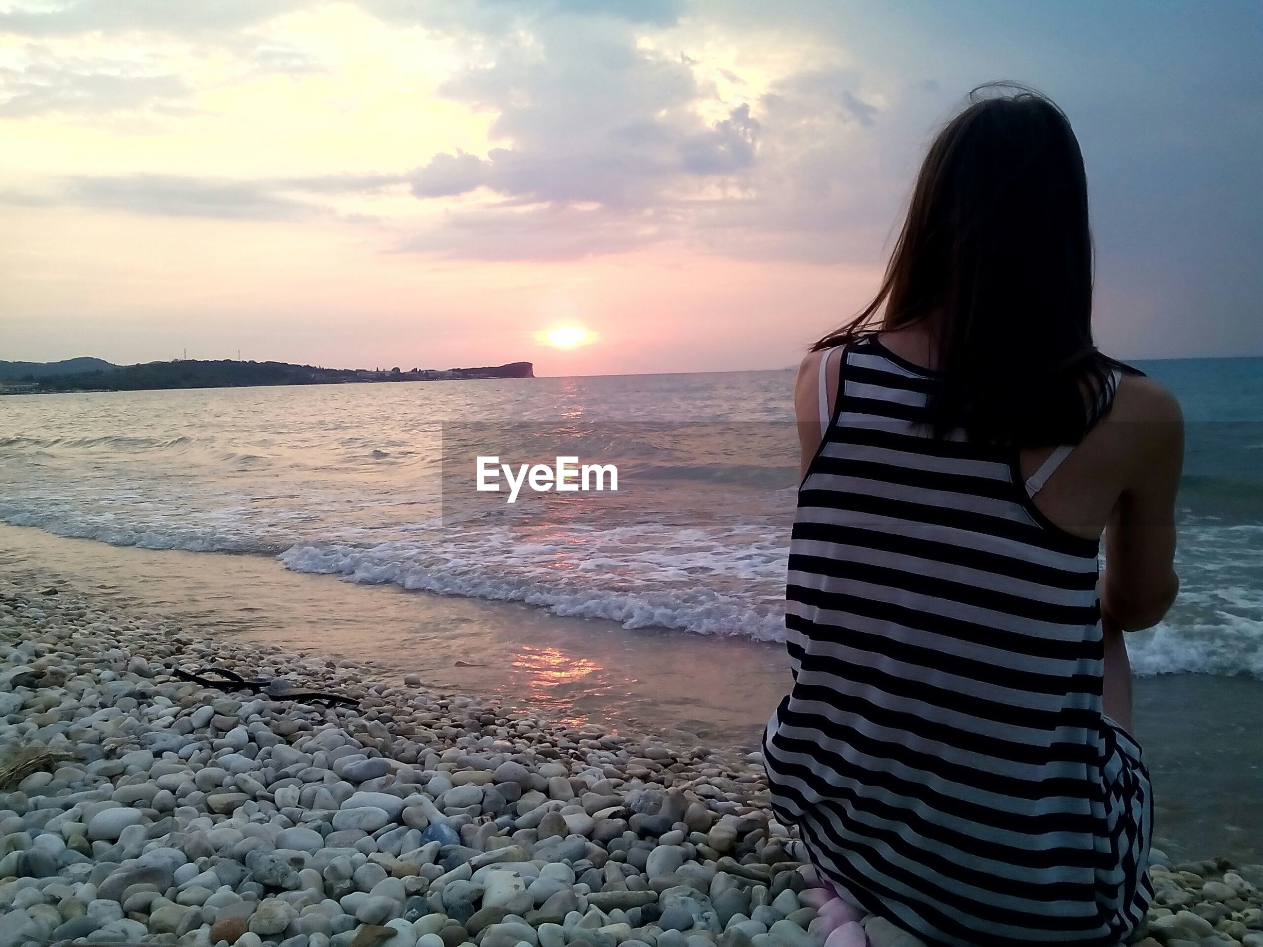 Rear view of woman sitting at beach against sky during sunset