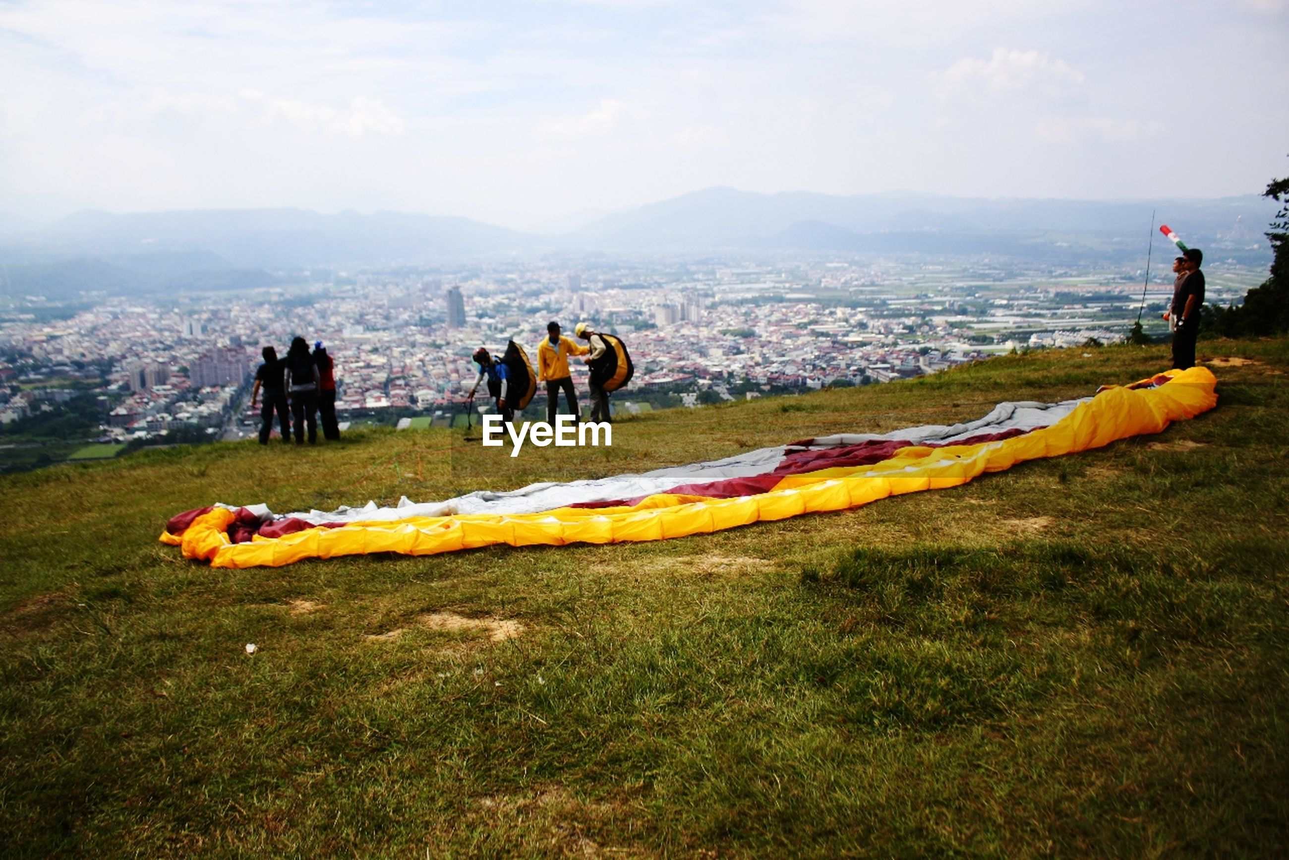 People with parachutes on grassland against cityscape