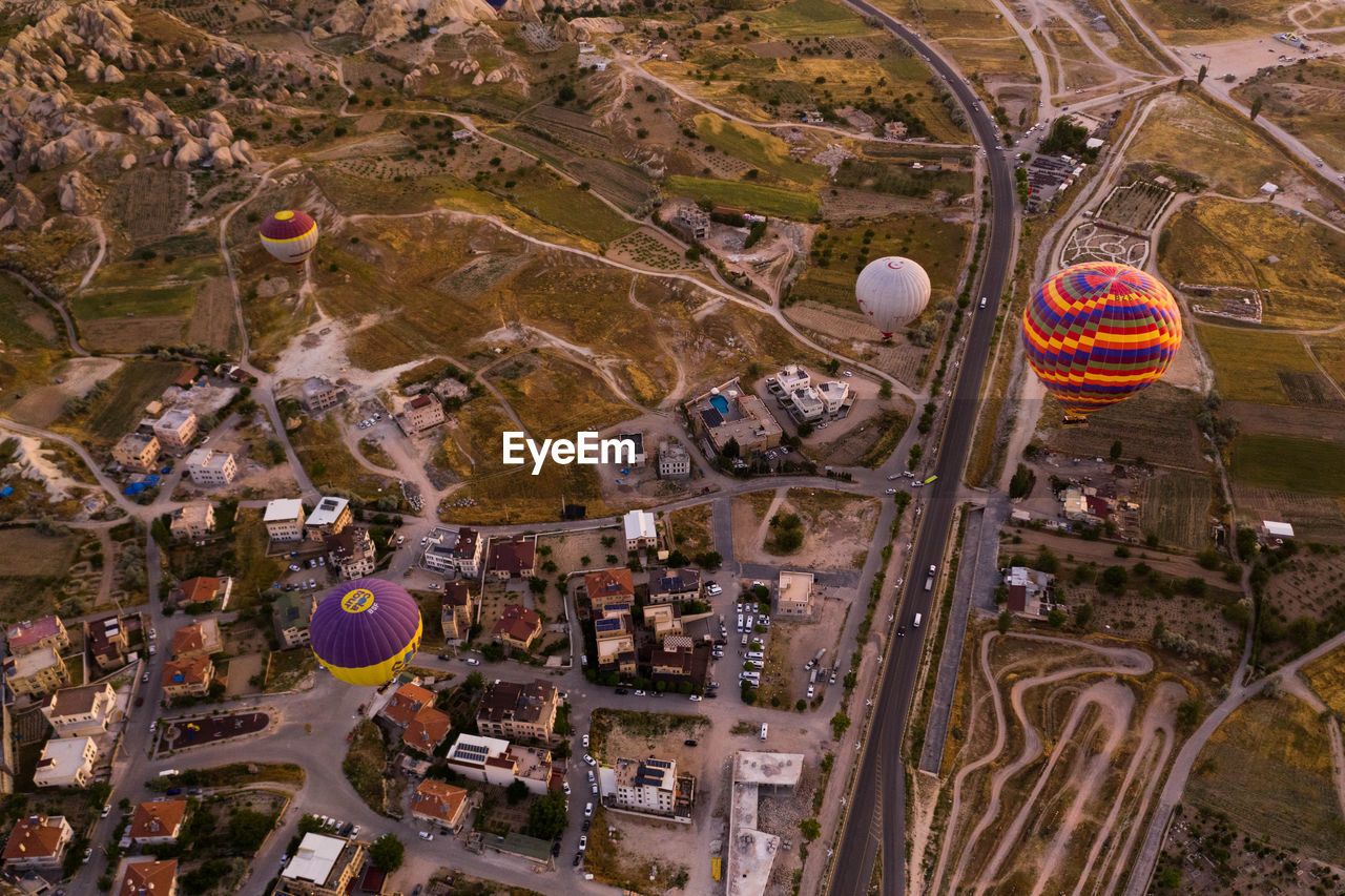 architecture, building exterior, aerial view, travel destinations, transportation, built structure, city, high angle view, nature, air vehicle, day, balloon, outdoors, mode of transportation, flying, travel, hot air balloon, road, sport, cityscape