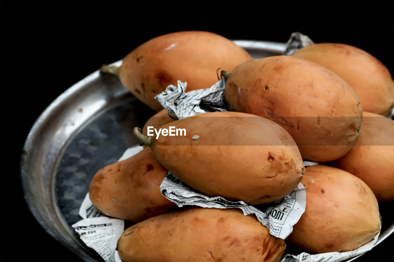 High Angle View Of Papayas In Plate Against Black Background
