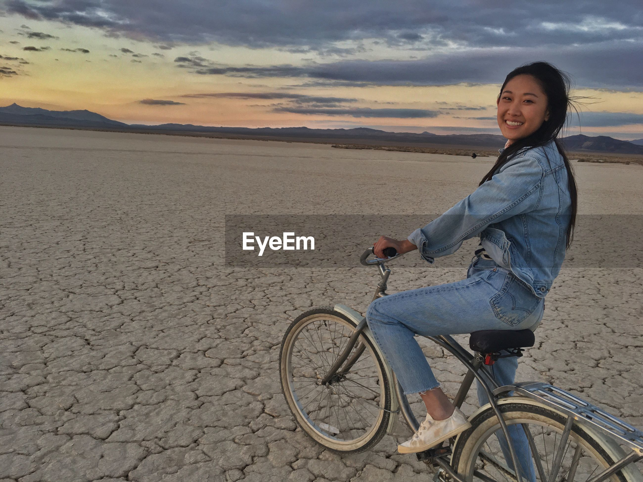 Portrait of smiling young woman riding bicycle on cracked field at sunset