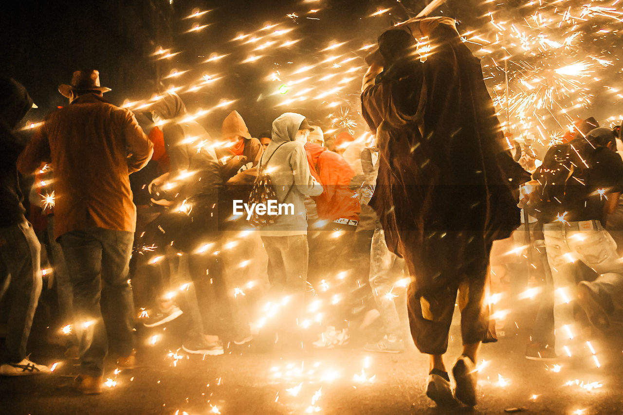 People Amidst Firework Sparks At Night