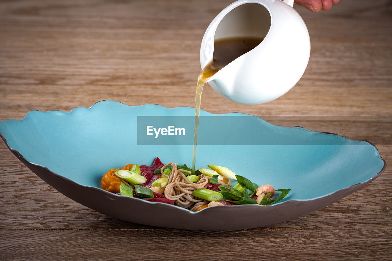 Broth being poured on food in bowl on table