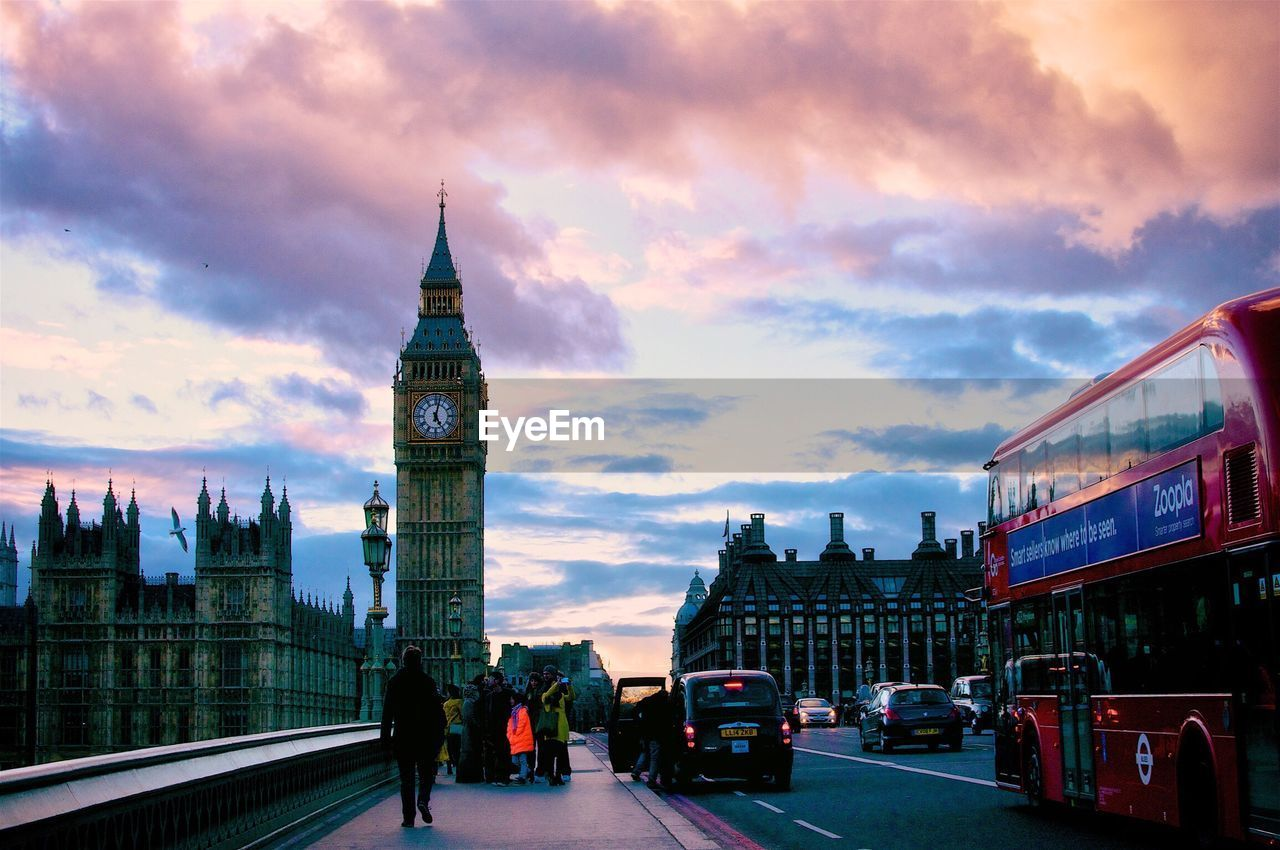 cloud - sky, architecture, sky, built structure, transportation, land vehicle, mode of transport, building exterior, travel, travel destinations, car, tower, city, real people, clock tower, outdoors, double-decker bus, day, men