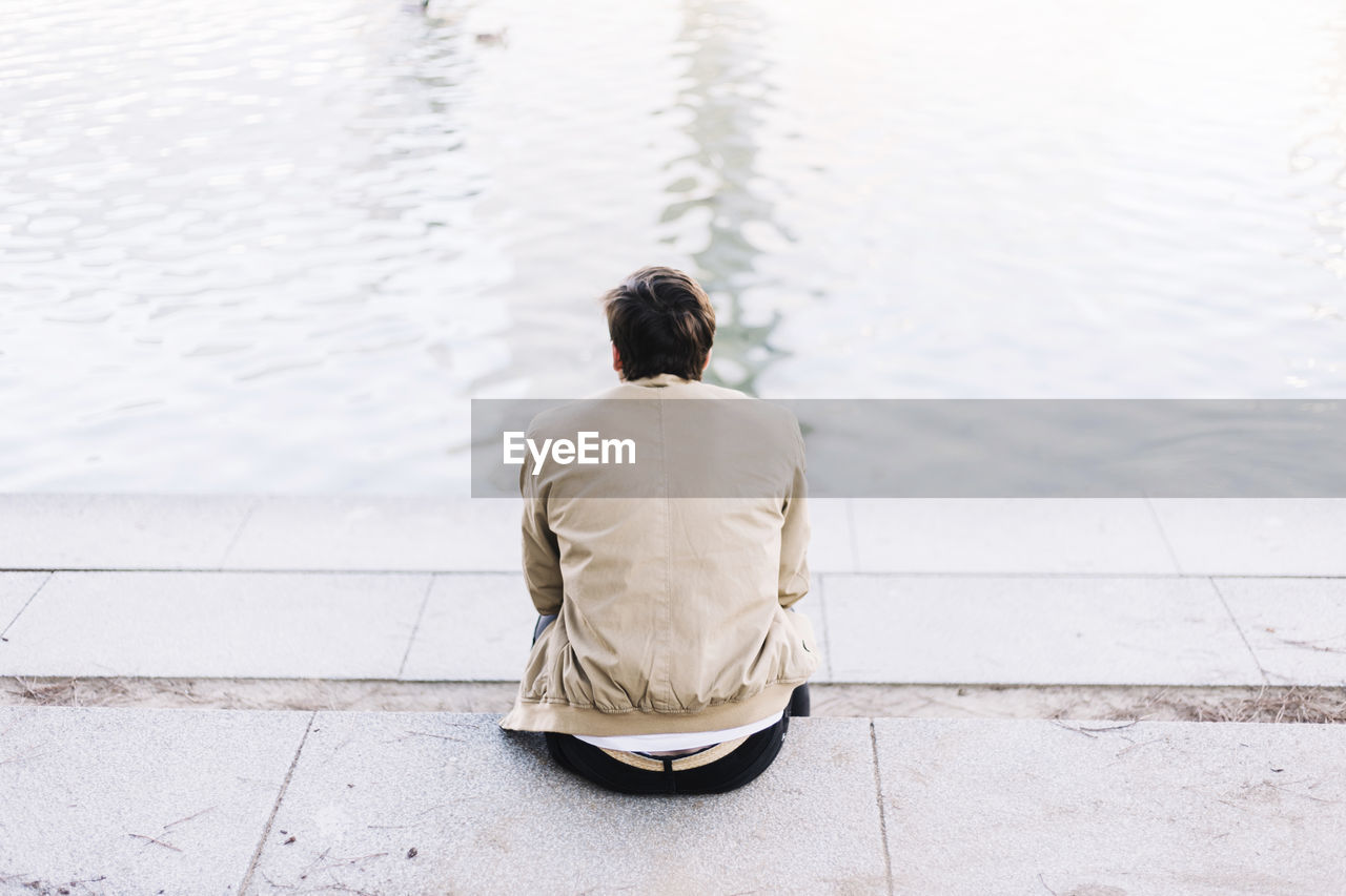 Rear view of man sitting on promenade at lakeshore