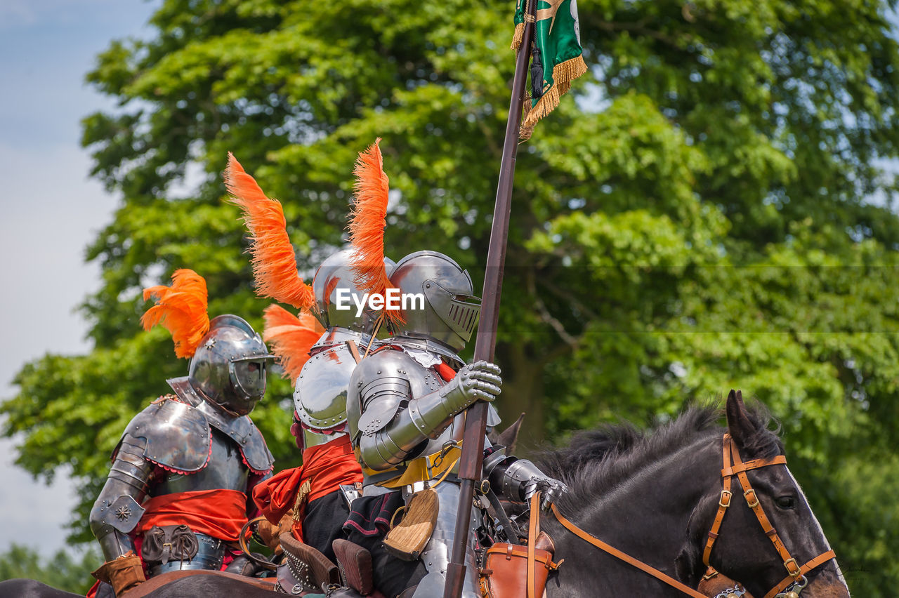 Men riding horses on field against sky