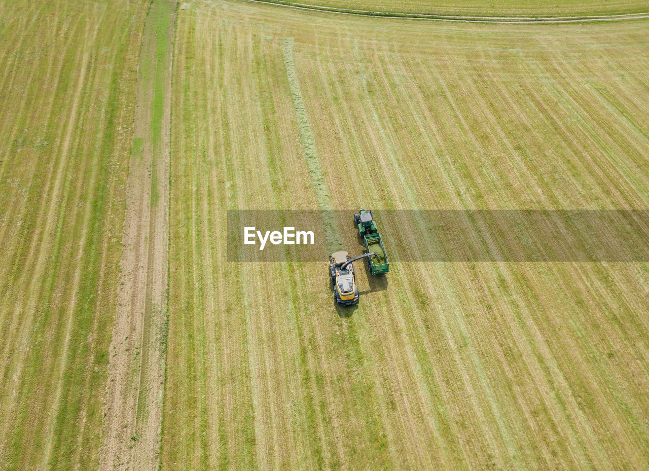 Aerial view of tractor on agricultural landscape during sunny day