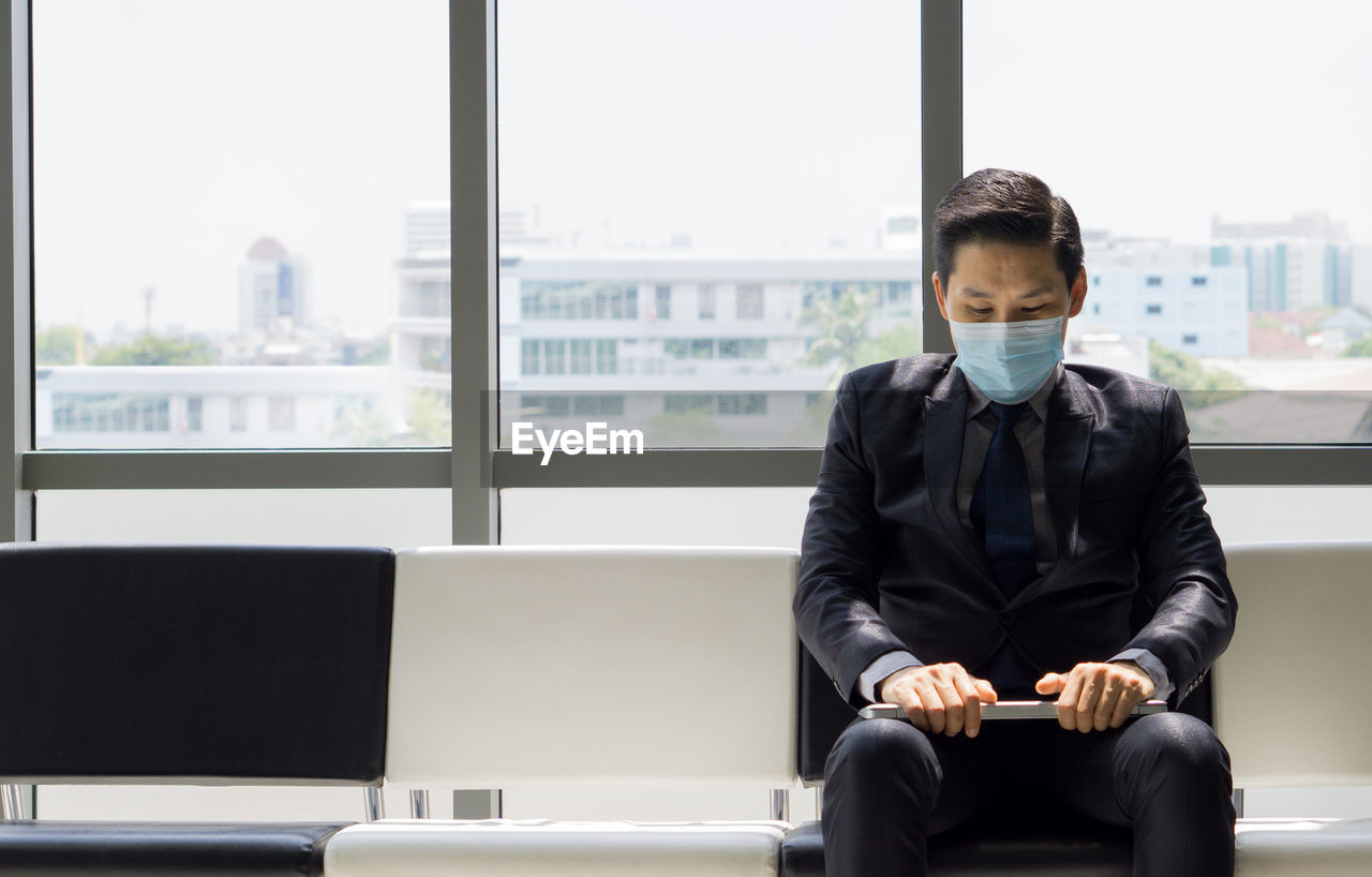 Man with mask sitting in waiting room in office