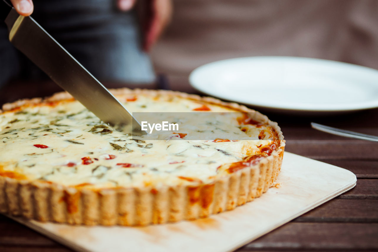 Cropped Hand Cutting Quiche With Tomatoes On Cutting Board On Table