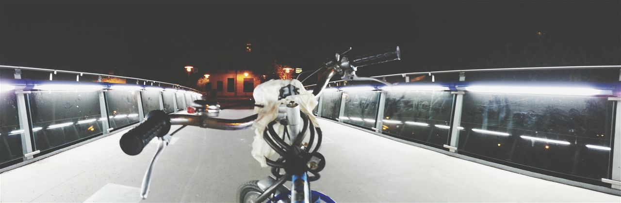 Panoramic view of bicycle on walkway at night