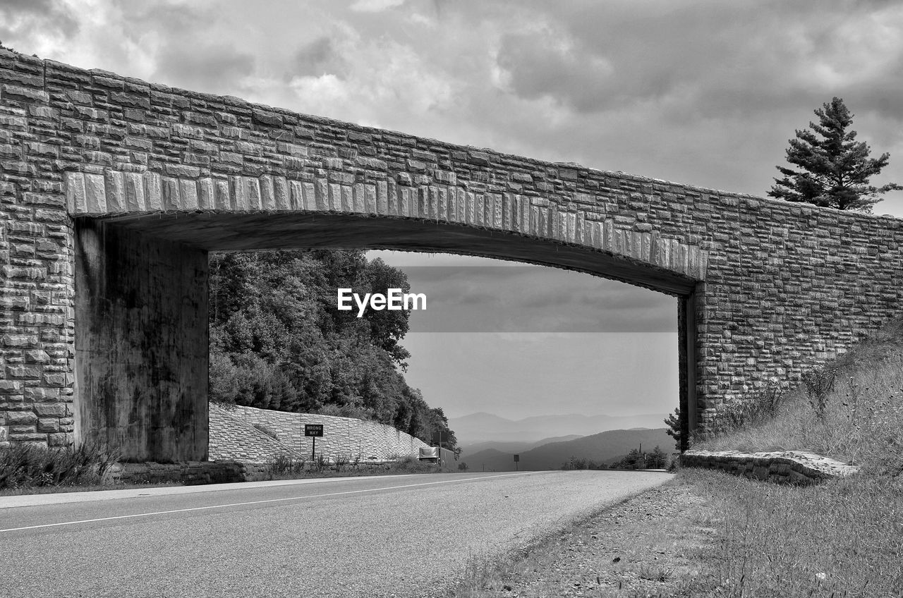architecture, built structure, sky, cloud - sky, transportation, nature, day, connection, no people, arch, bridge, road, building exterior, bridge - man made structure, the way forward, outdoors, direction, wall, plant, mountain, stone wall