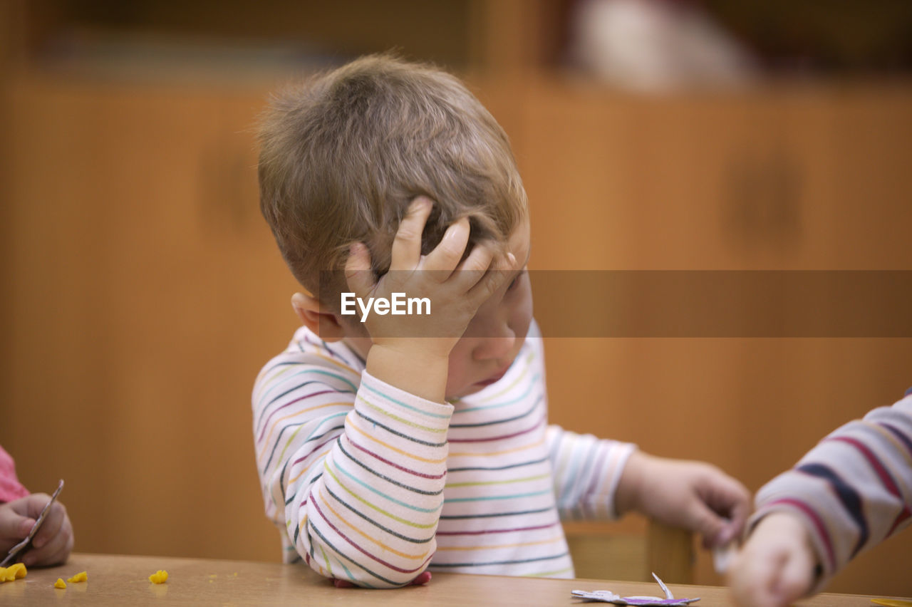 Close-up of worried boy sitting on table at classroom