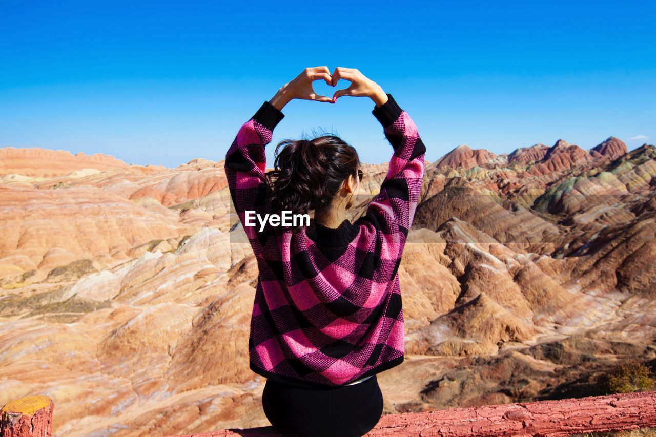 Rear view of young woman making heart shape while sitting on wooden railing against clear blue sky during sunny day