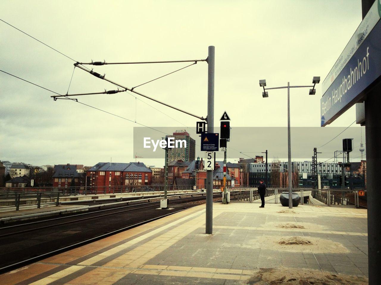 transportation, sky, railroad track, rail transportation, cable, outdoors, cloud - sky, day, public transportation, no people, building exterior, built structure, railway signal, architecture, nature, city
