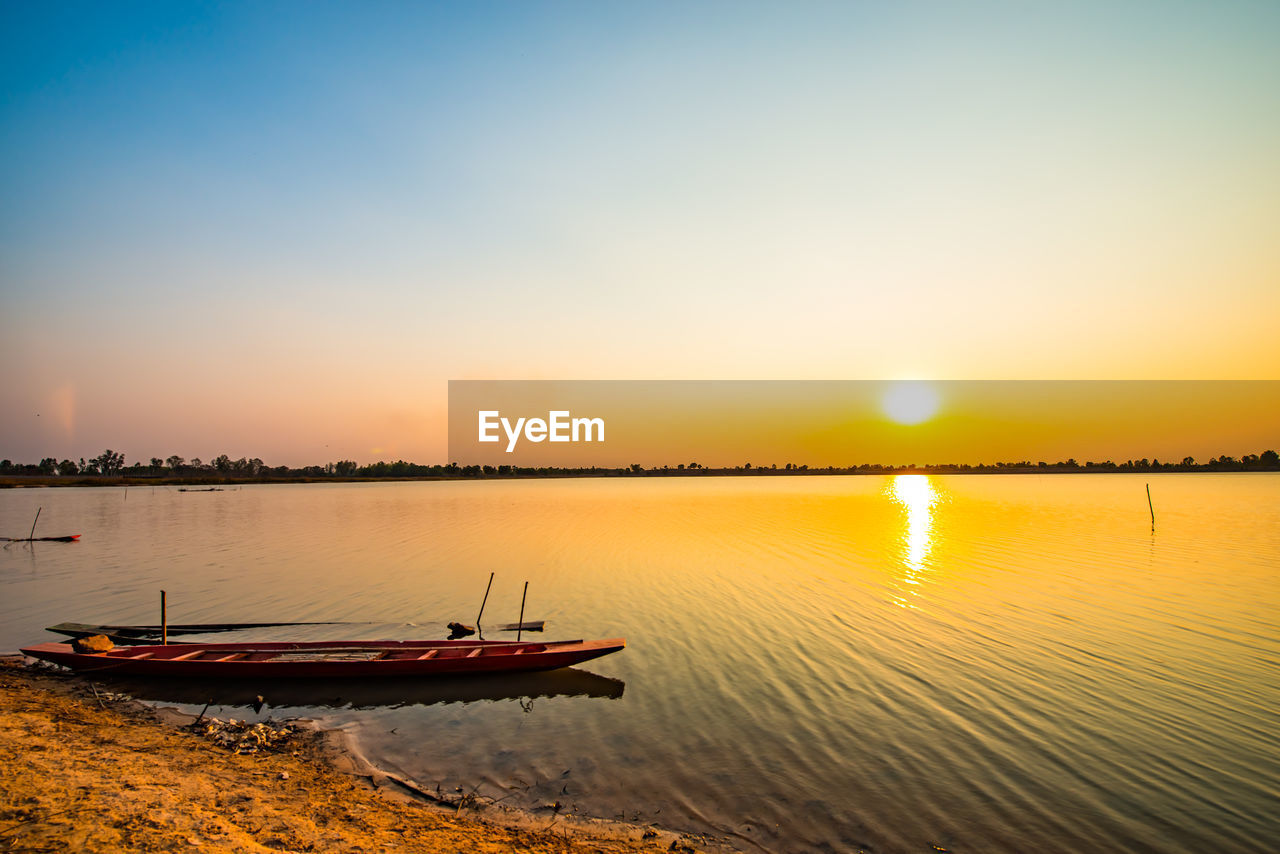 sunset, sky, water, nautical vessel, transportation, mode of transportation, scenics - nature, beauty in nature, tranquility, reflection, tranquil scene, nature, orange color, lake, moored, no people, non-urban scene, waterfront, sun, outdoors, sailboat, rowboat