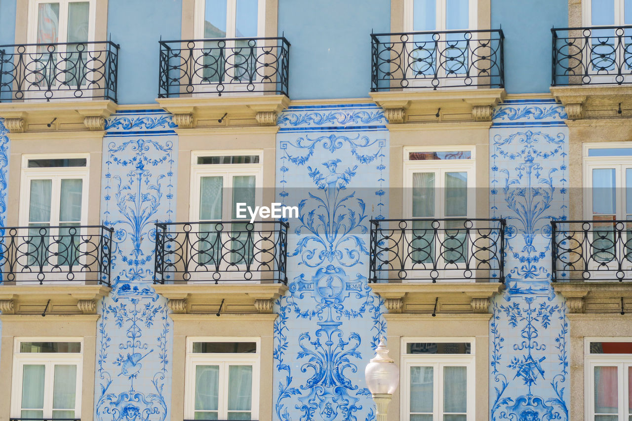 architecture, built structure, building exterior, window, building, residential district, low angle view, no people, pattern, blue, day, balcony, city, full frame, creativity, art and craft, design, backgrounds, outdoors, wall - building feature, architectural column, floral pattern