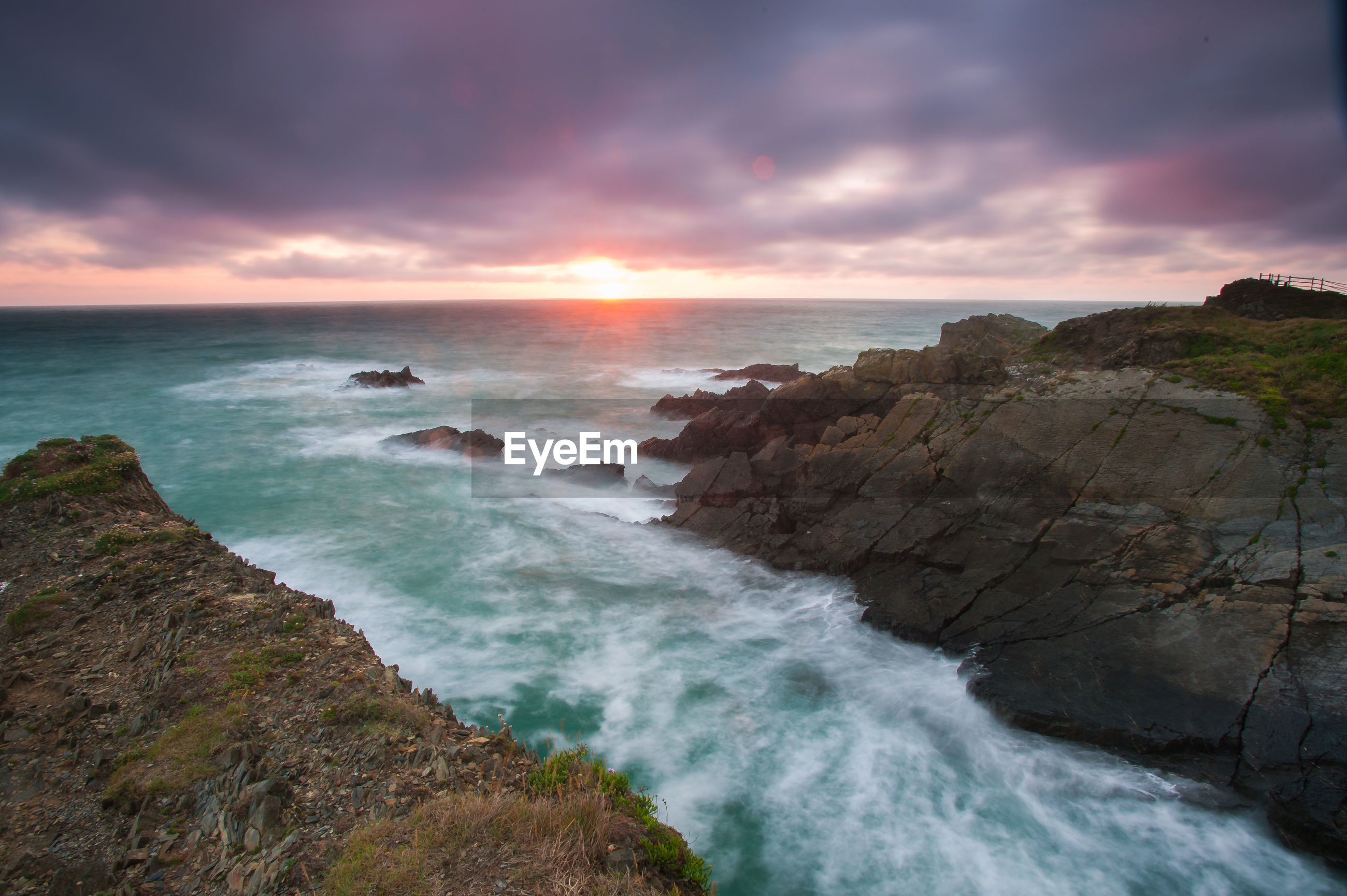 SCENIC VIEW OF ROCKY BEACH AGAINST SKY DURING SUNSET