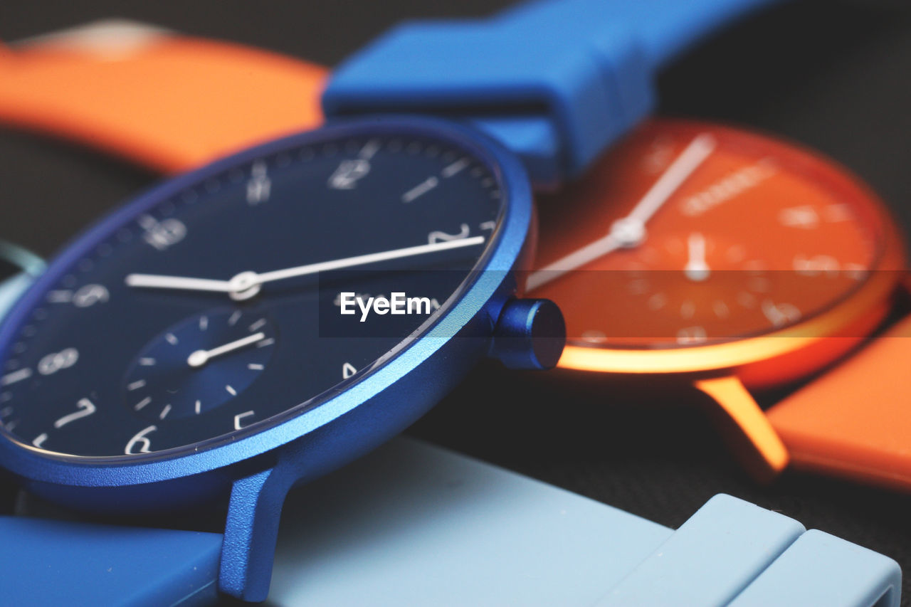 close-up, indoors, time, wristwatch, clock, no people, still life, orange color, watch, number, accuracy, instrument of time, personal accessory, communication, technology, selective focus, focus on foreground, clock hand, blue, red, minute hand, clock face, stopwatch, electrical equipment