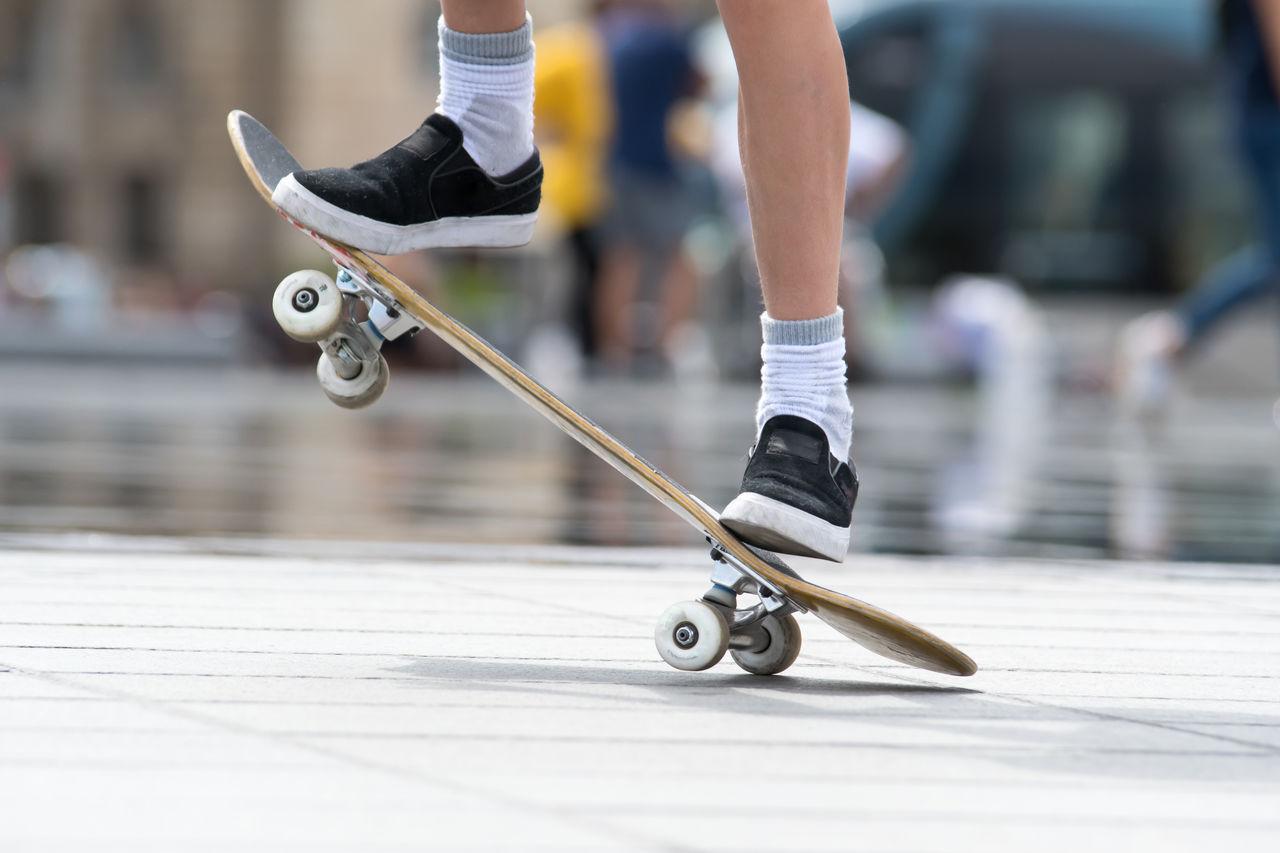 Low Section Of Man Skateboarding At Skateboard Park