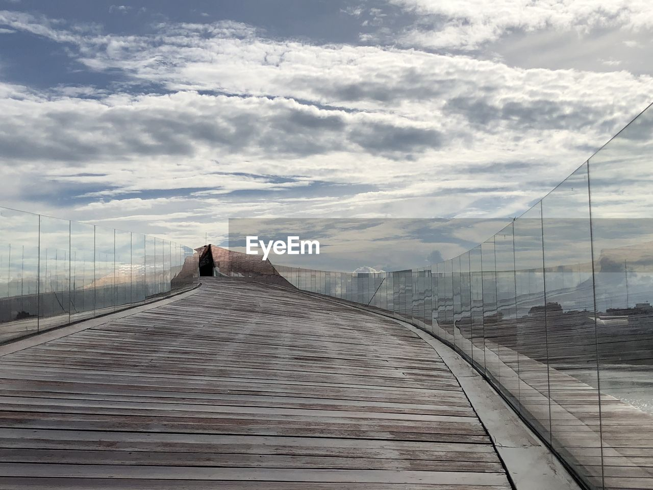 cloud - sky, sky, architecture, direction, built structure, the way forward, nature, day, outdoors, diminishing perspective, building exterior, city, one person, railing, wood - material, real people, connection, vanishing point, skyscraper