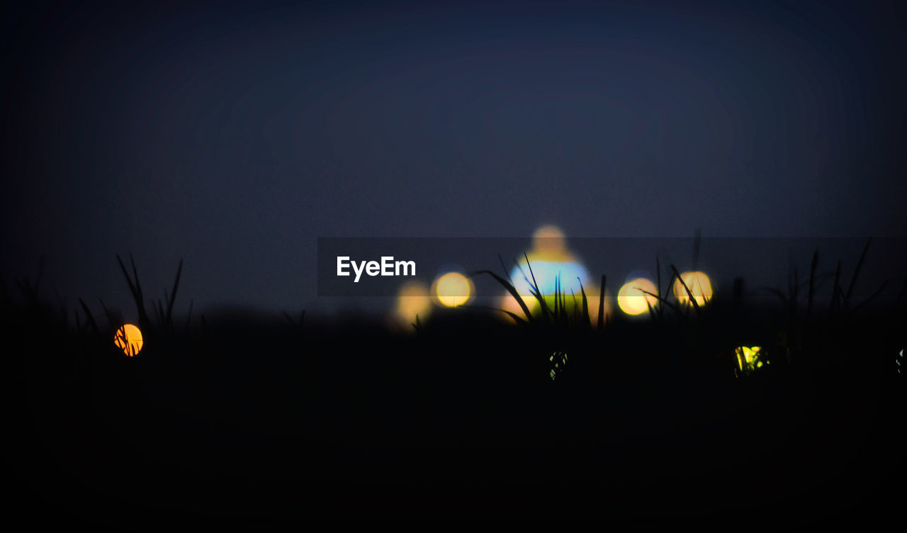 sky, night, illuminated, no people, copy space, silhouette, nature, beauty in nature, lighting equipment, sunset, outdoors, glowing, dark, defocused, clear sky, yellow, light - natural phenomenon, moon, tranquility, dusk, light