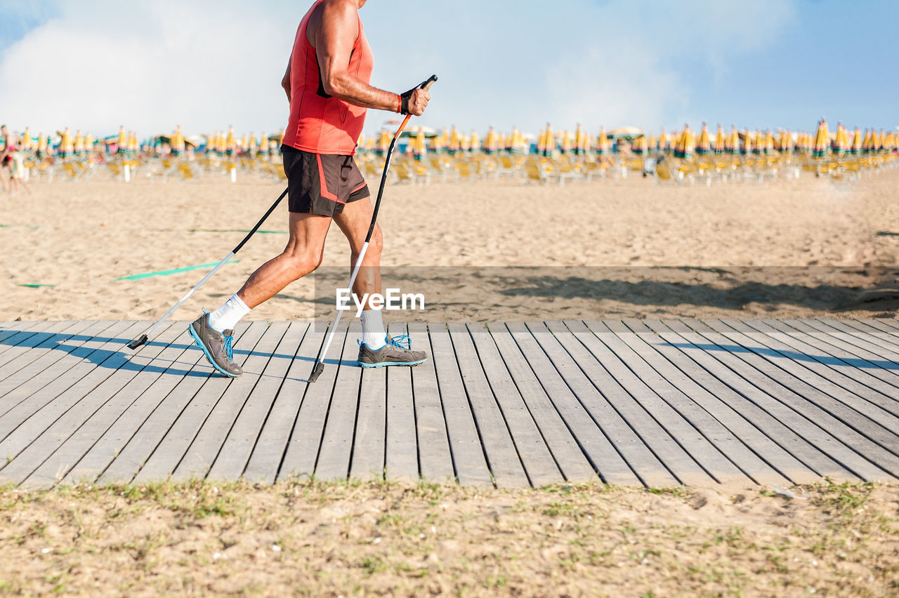Man With Poles Running On Boardwalk