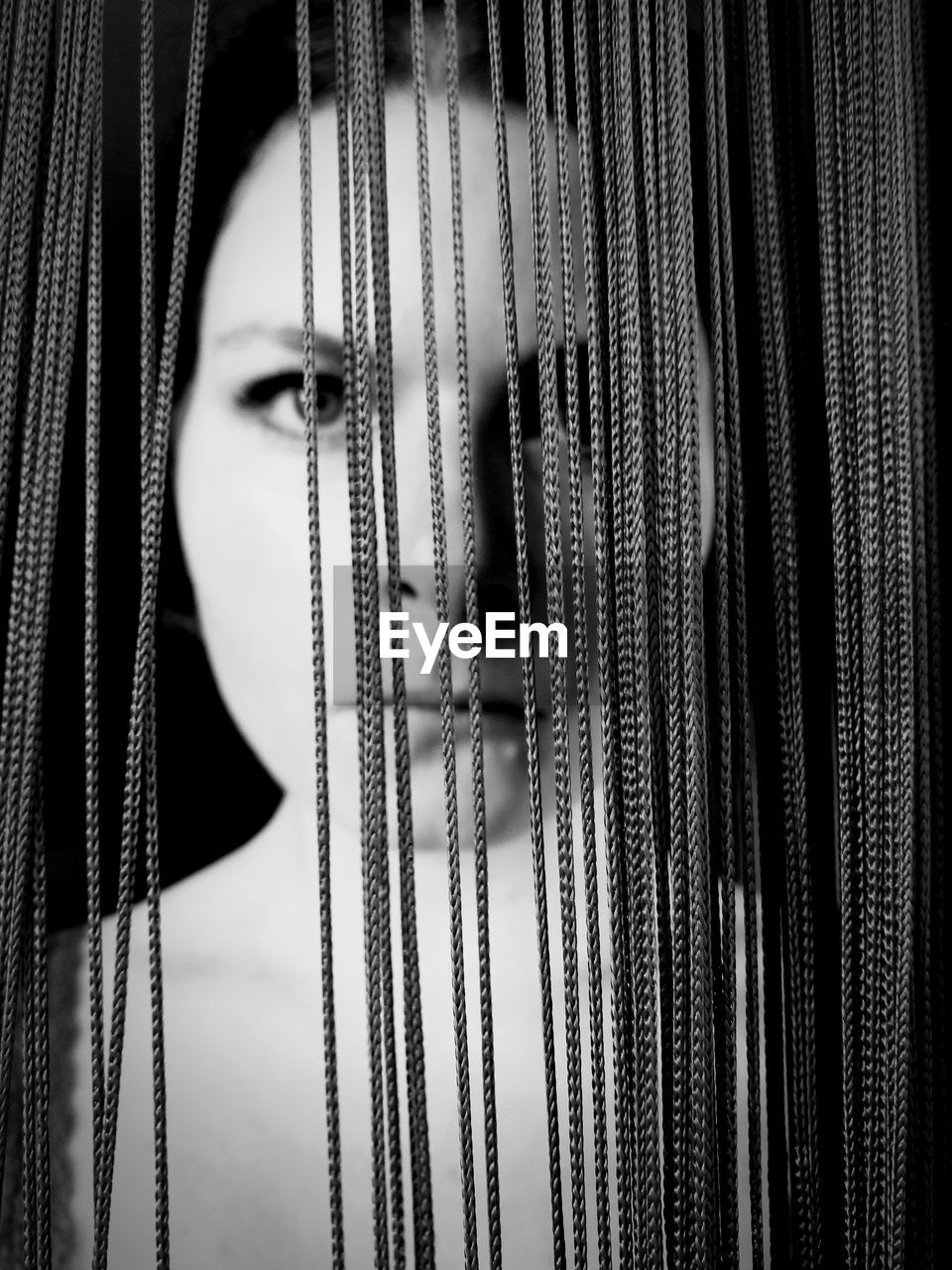 Close-Up Portrait Of Woman Standing Behind Strings Against Black Background