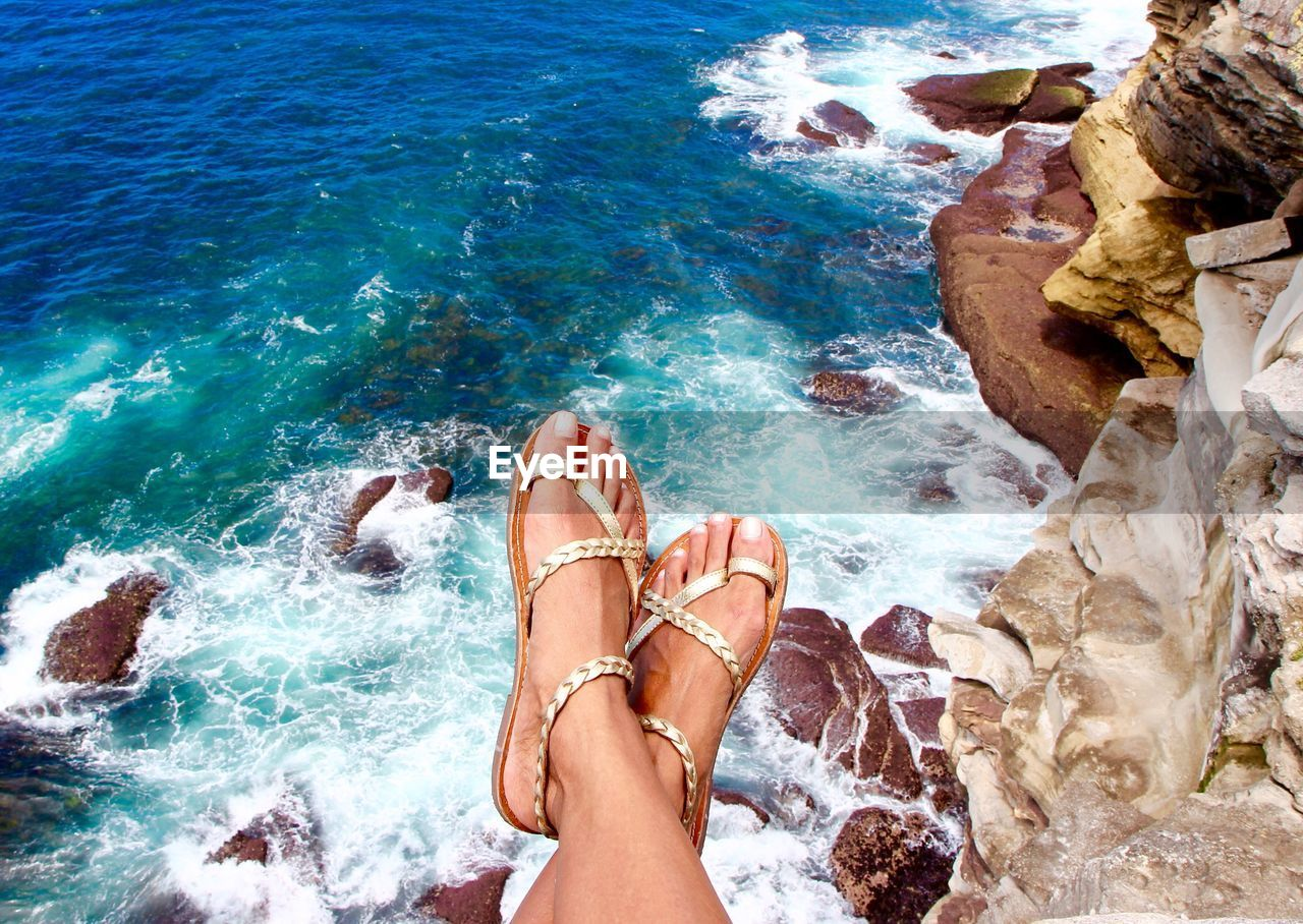 human body part, water, sea, rock, low section, body part, rock - object, solid, human leg, people, leisure activity, personal perspective, human foot, barefoot, nature, lifestyles, motion, adult, outdoors, human limb
