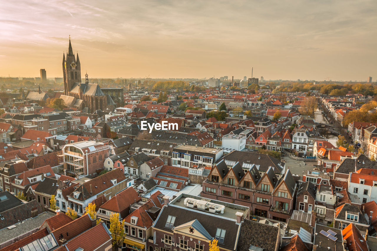 building exterior, architecture, built structure, city, cityscape, building, sky, residential district, crowd, high angle view, roof, crowded, cloud - sky, nature, sunset, religion, town, community, place of worship, outdoors, townscape, settlement