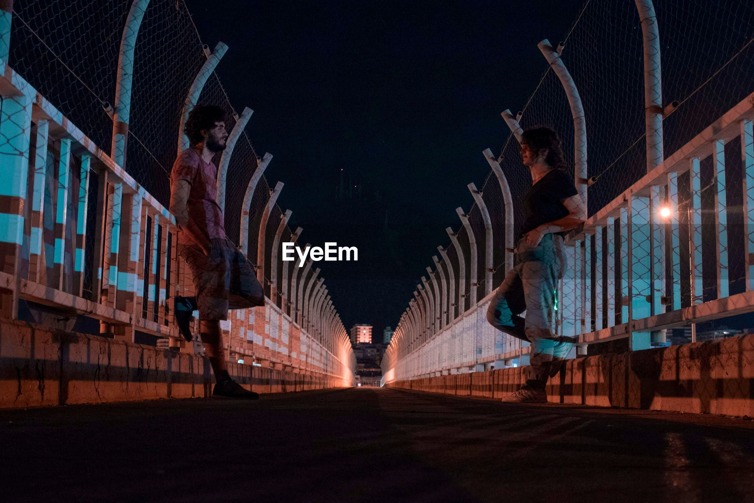 Side view of people standing on bridge against sky in city at night