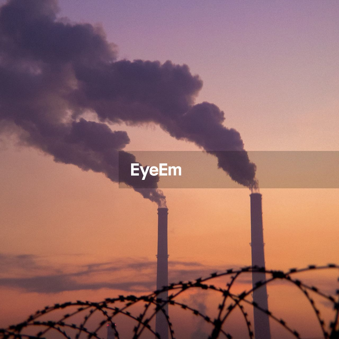 Low Angle View Of Factory Emitting Smoke Against Sky During Sunset