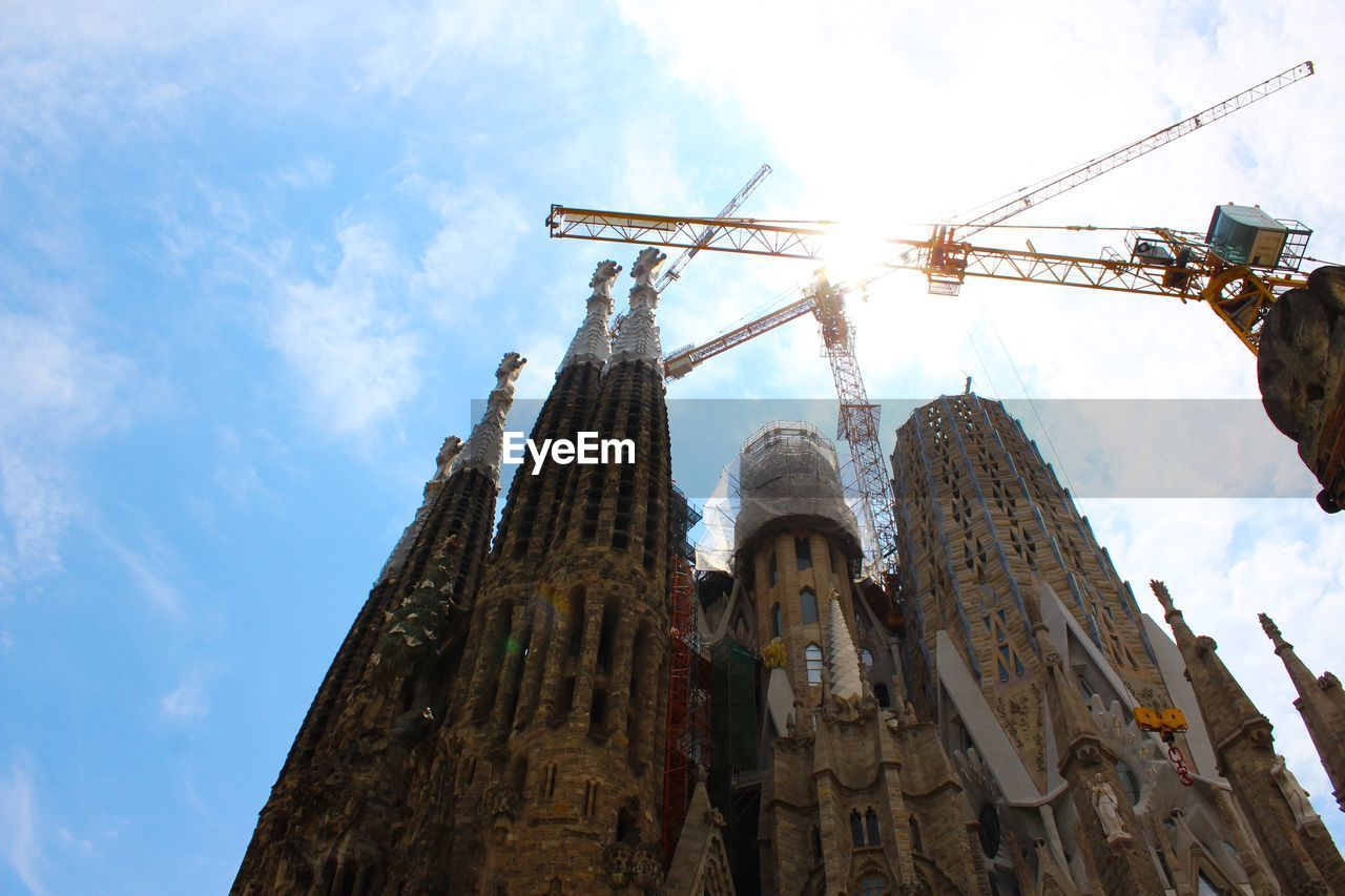 low angle view, sky, cloud - sky, spirituality, belief, religion, place of worship, architecture, built structure, day, nature, building, no people, building exterior, crane - construction machinery, the past, outdoors