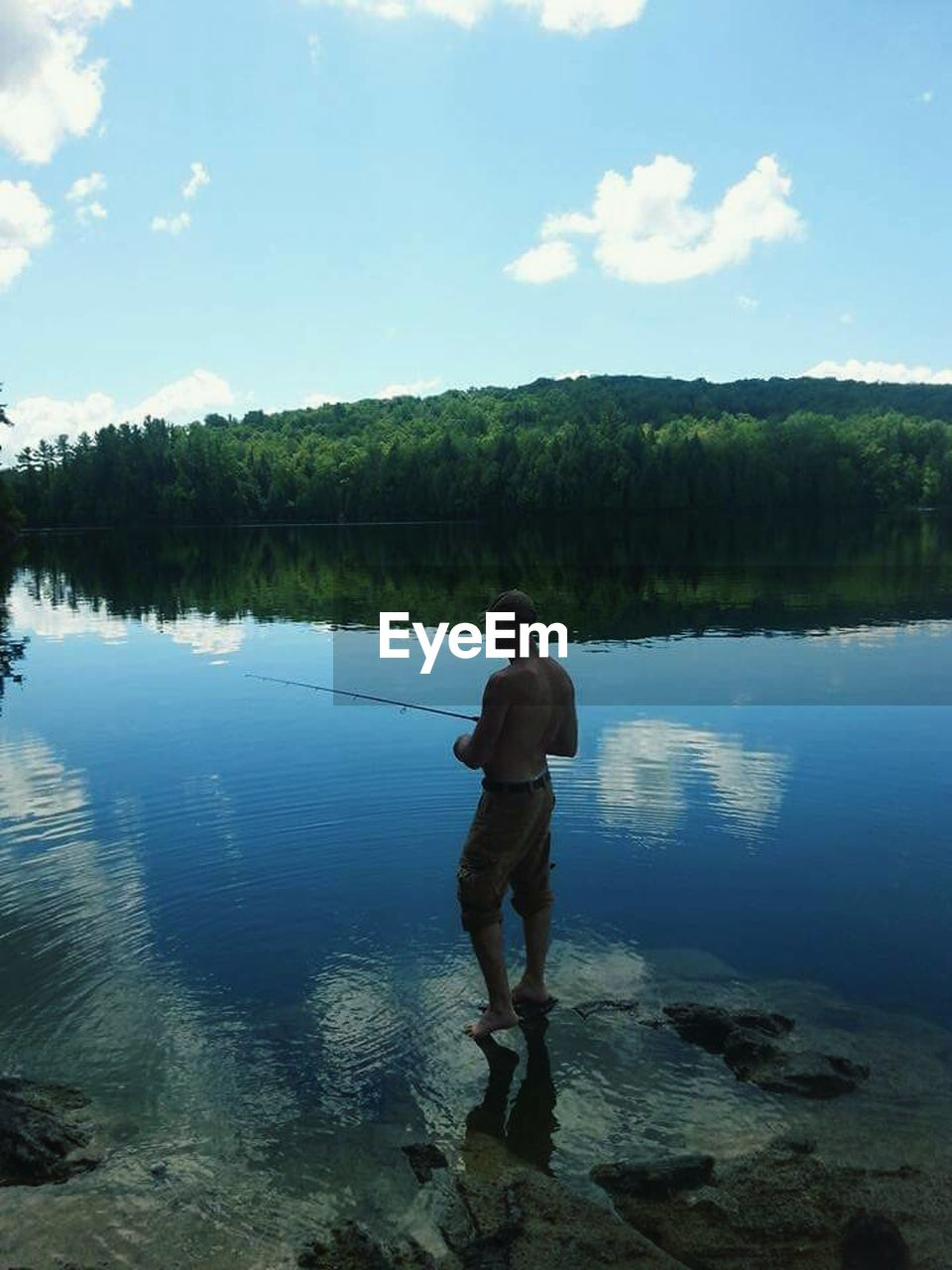 water, full length, nature, one person, sky, standing, real people, tree, lake, leisure activity, shirtless, rear view, beauty in nature, reflection, day, outdoors, scenics, tranquility, lifestyles, growth, men, ankle deep in water, people