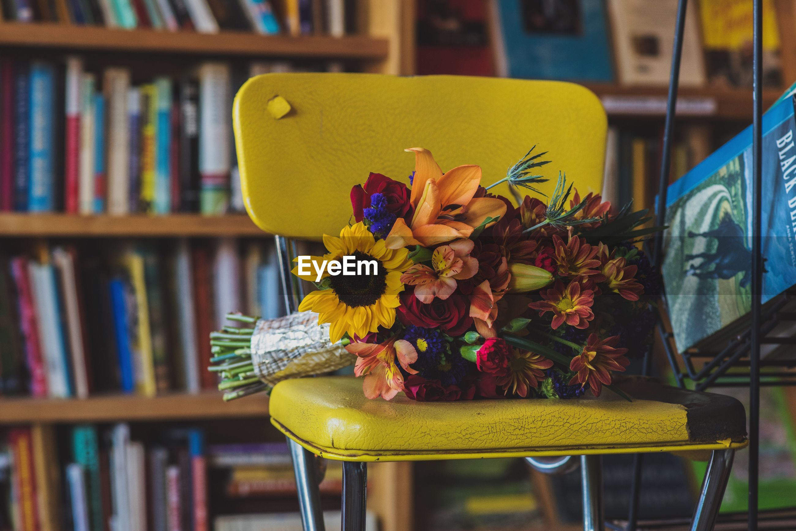 Close-up of yellow bouquet on chair