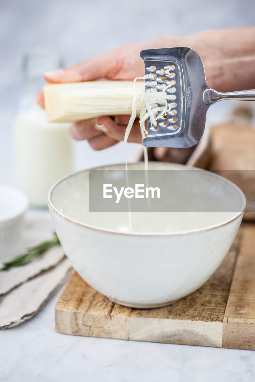Cropped hands grating cheese in bowl on table